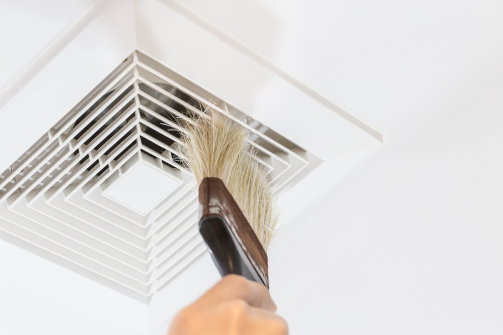 person cleaning air duct