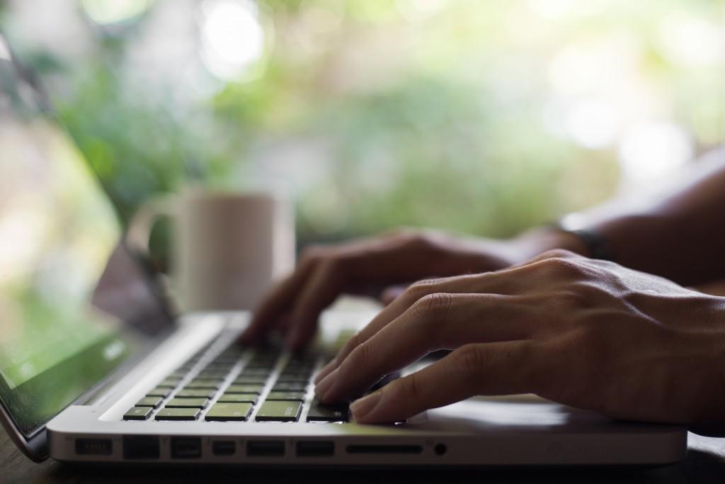 Hand typing laptop