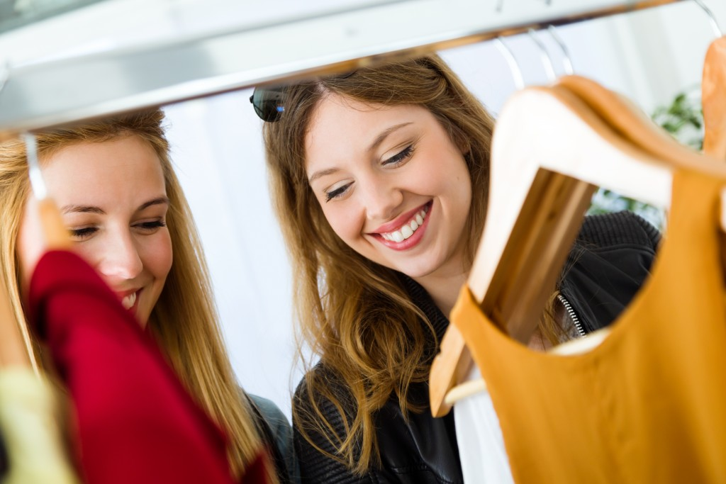 woman checking clothes in a store with friend