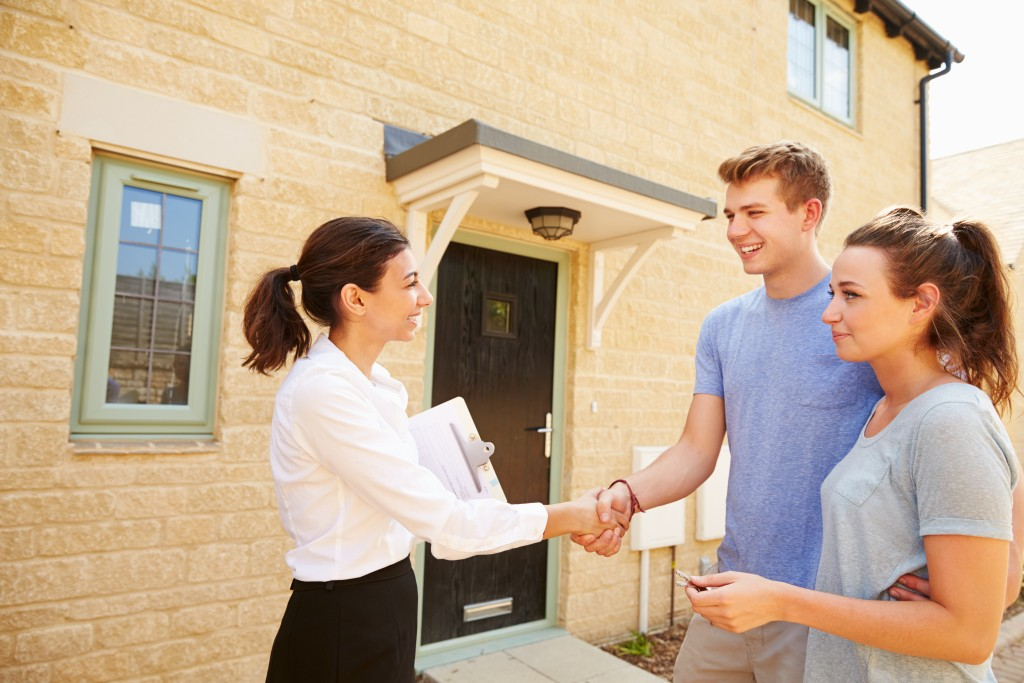 real estate agent shake hands with couple