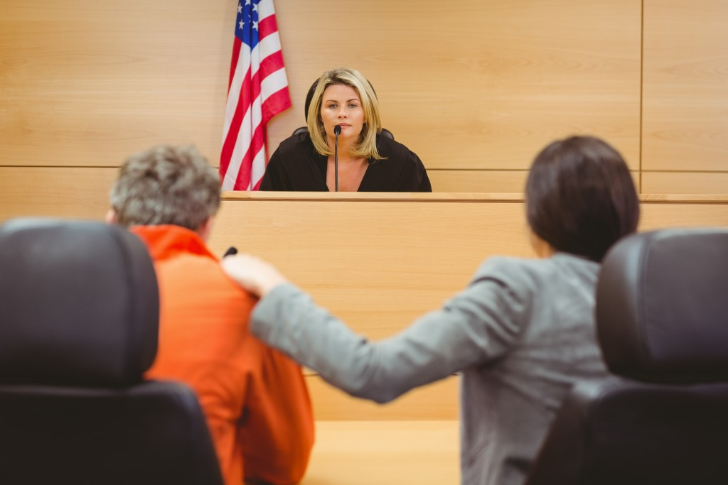 judge, lawyer, and the accused in a courtroom