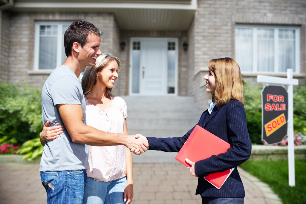 couple shaking hands with real estate agent