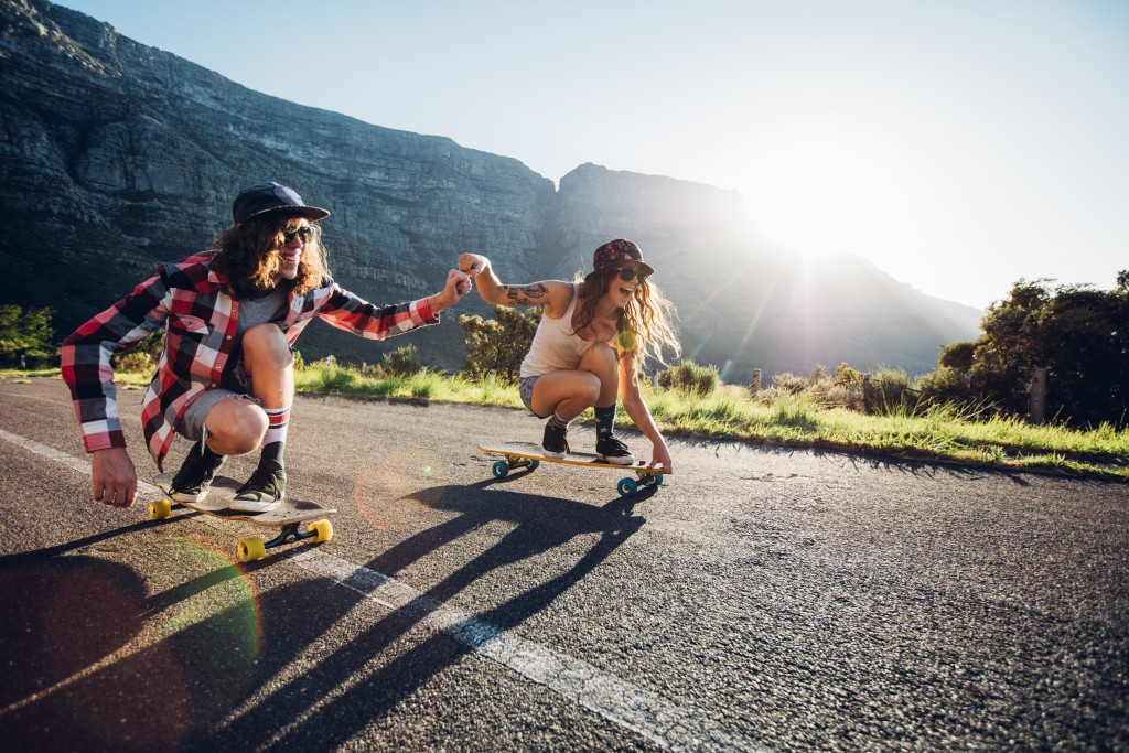Happy young couple having fun with skateboard on the road