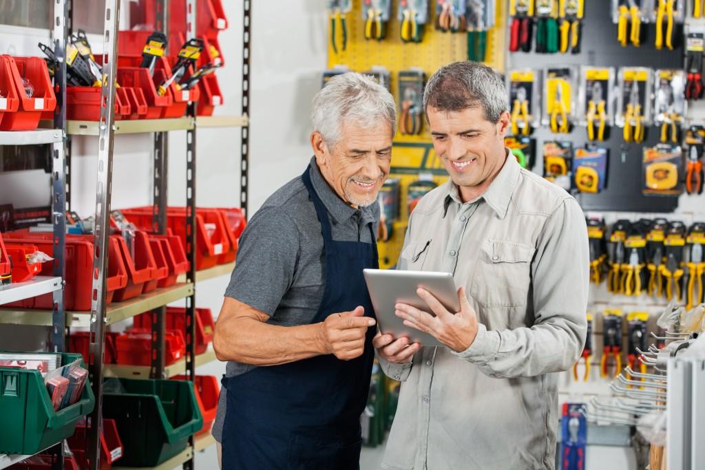 two men at a shop looking at tablet