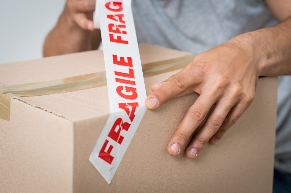 man placing a fragile sign on a box