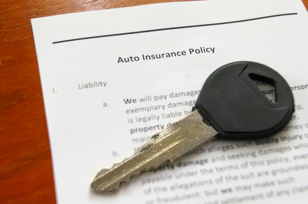 closeup of car key with an auto insurance policy
