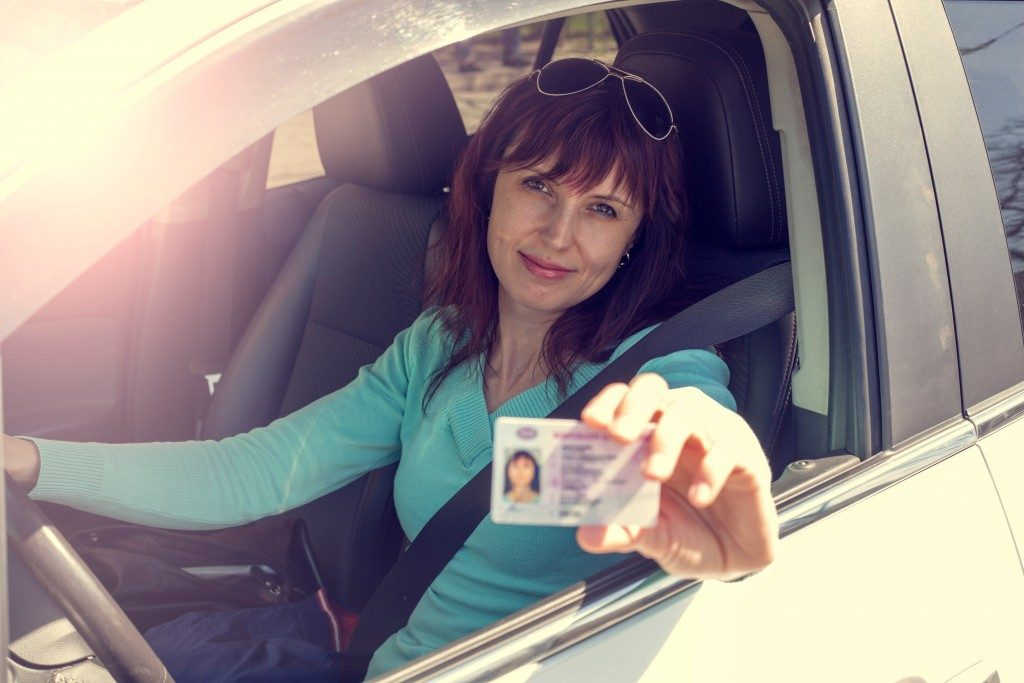 woman in the car showing her license