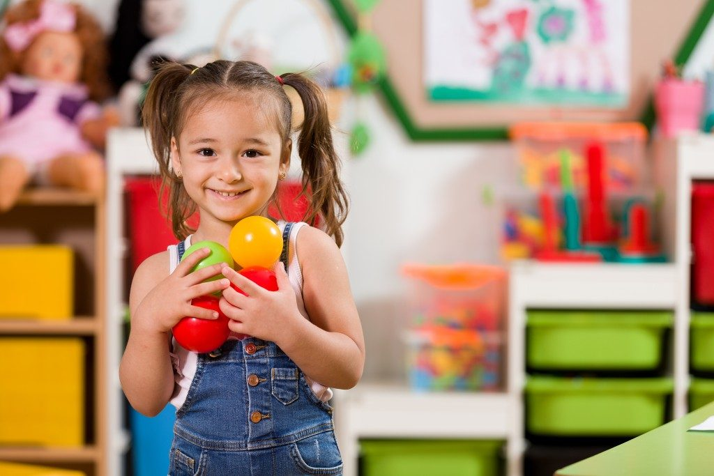 Preschooler holding colored balls