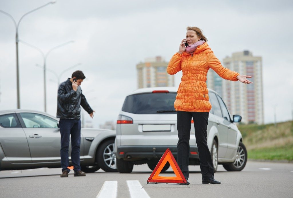 two people calling someone after an accident
