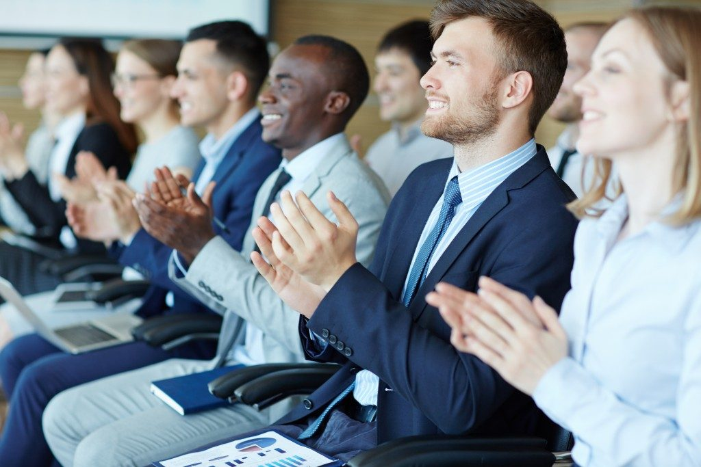 Employees clapping and wearing corporate attire