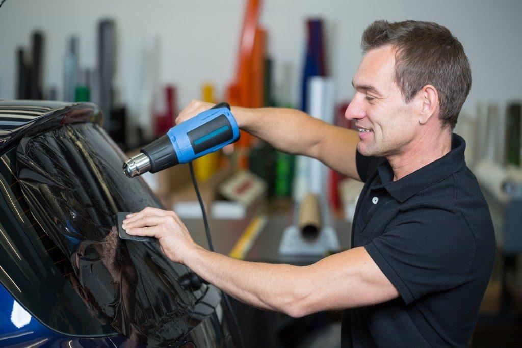 man applying tint to the car