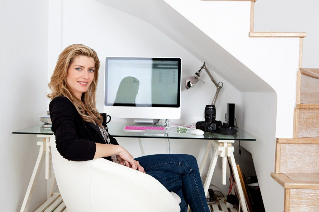 Young professional photographer working from home and sitting at her desk at home, with her camera equipment