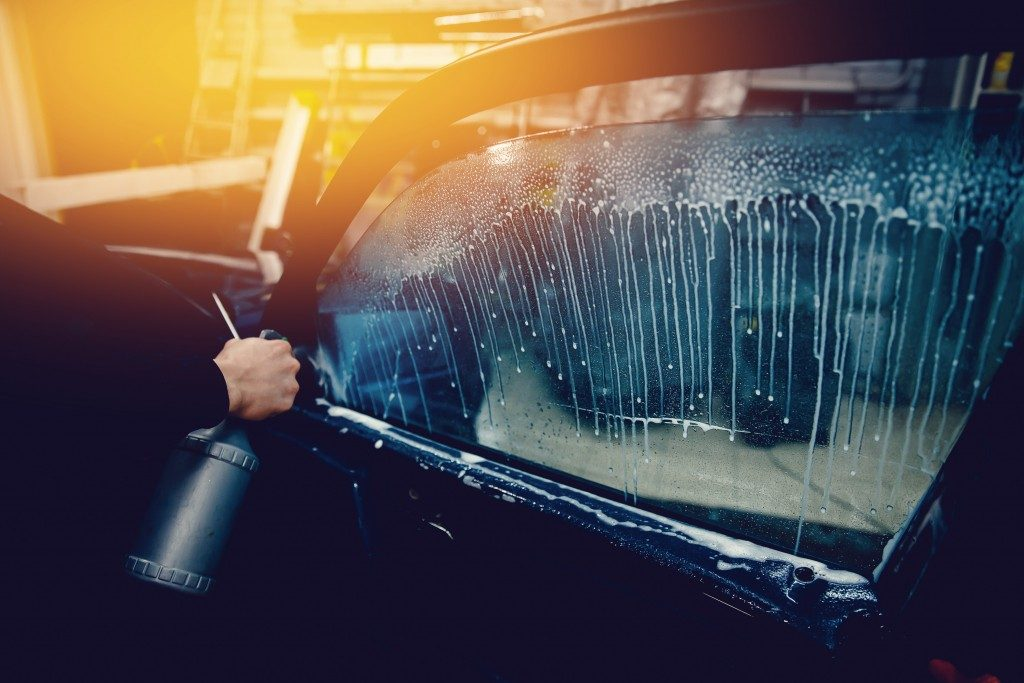 person preparing the car window for tinting