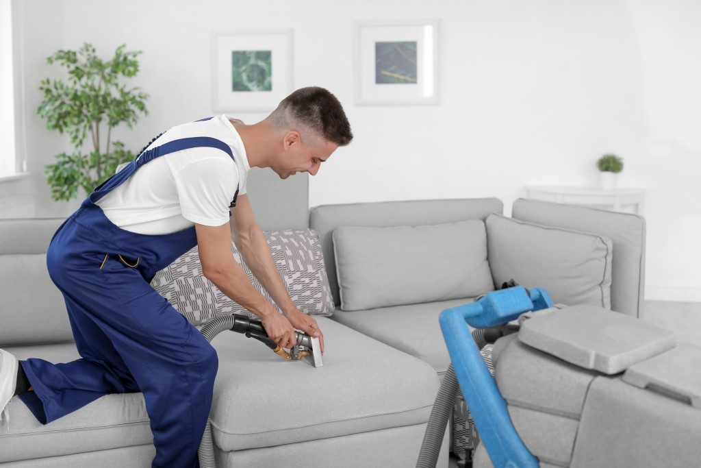 cleaner cleaning a home sofa