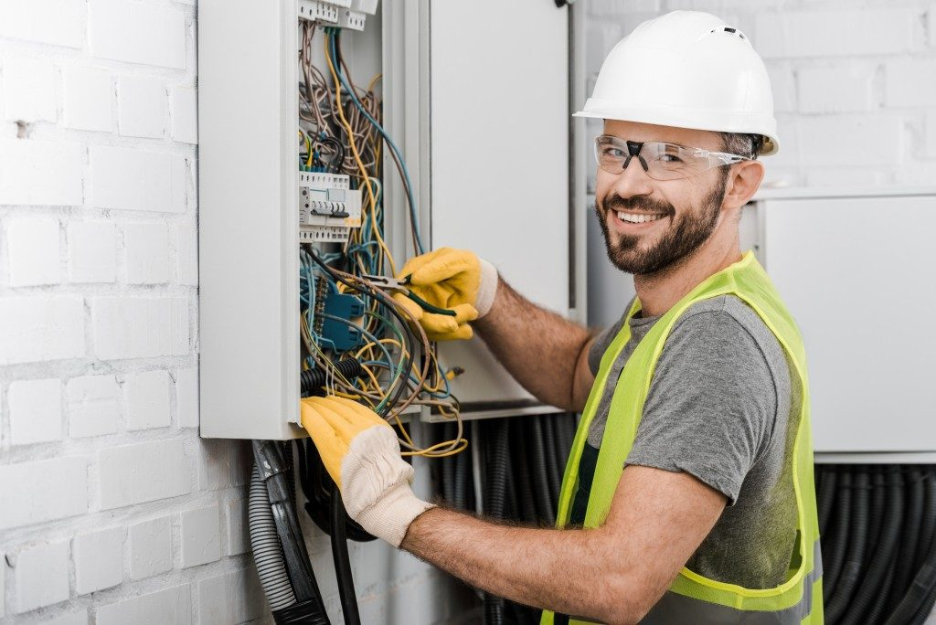 man fixing electrical fuses