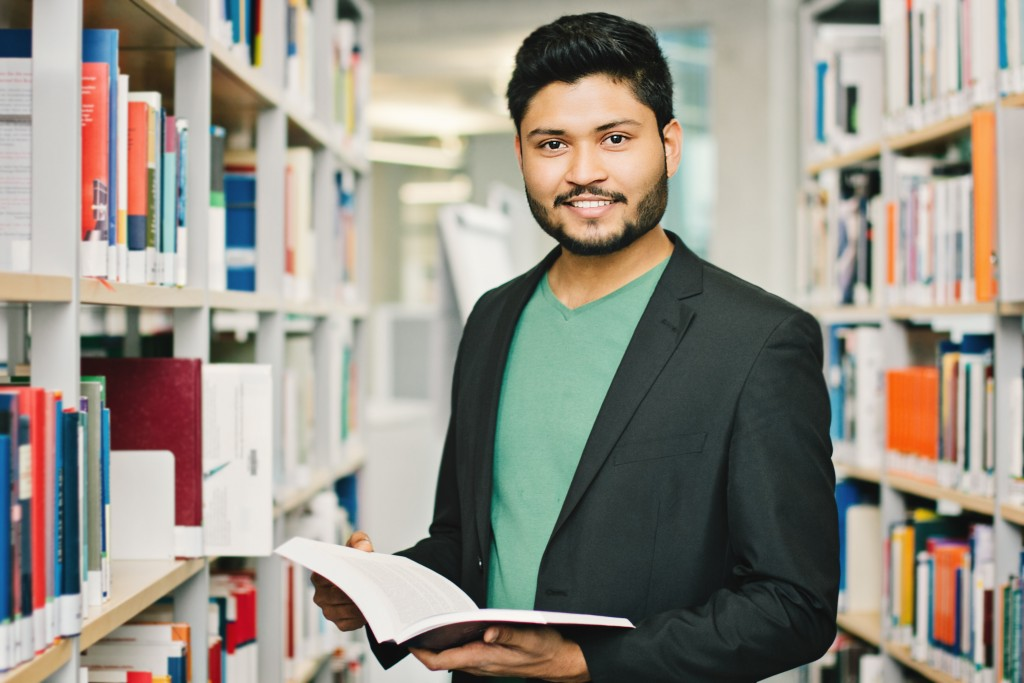 Male Indian student in the library