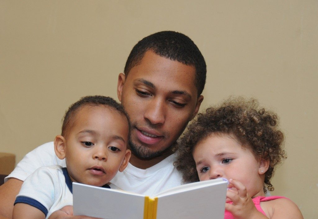Father reading book with children