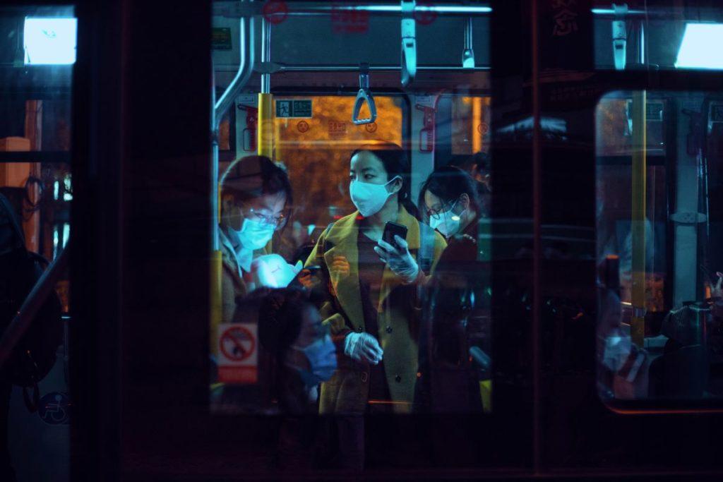 people on public transportation wearing facemasks