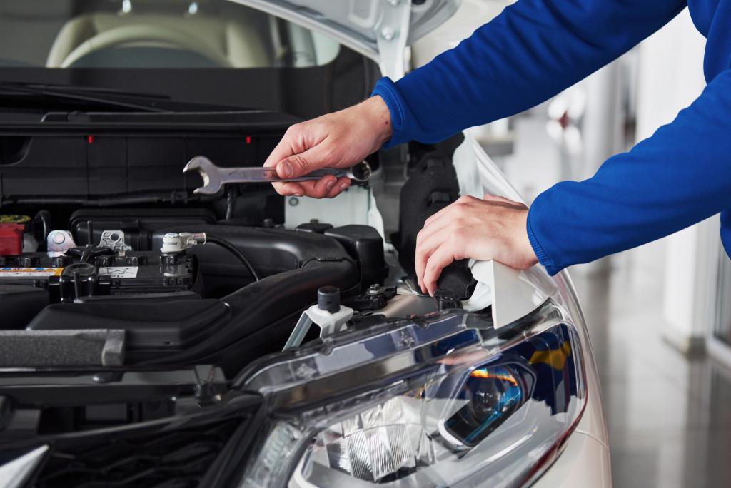 man inspecting car hood